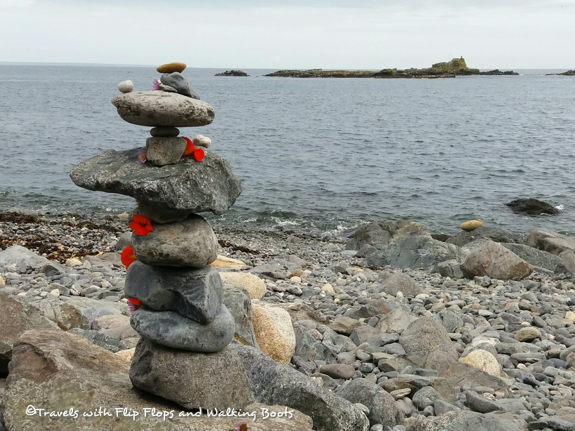 Mousehole gravity defying pebble tower decorated with nasturtium flowers