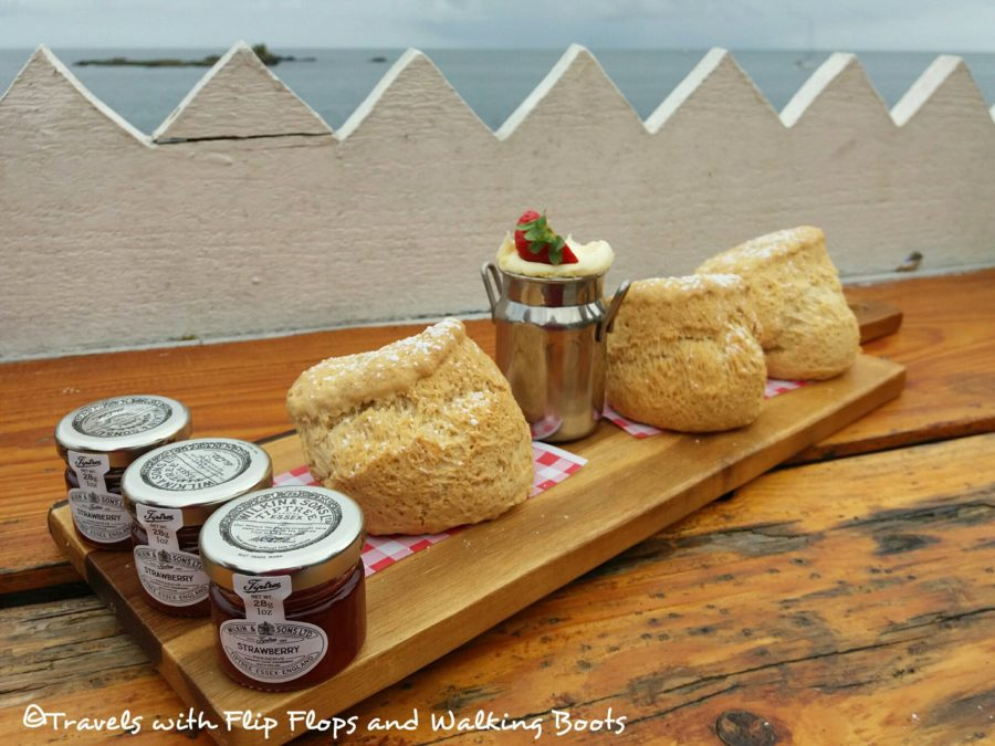 Cream tea for three, presented on a wooden paddle. comes with a free sea view and vintage china.